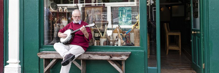 A man outside a pub playing Music. Enjoy musical tour of Ireland with Discover Ireland Tours.