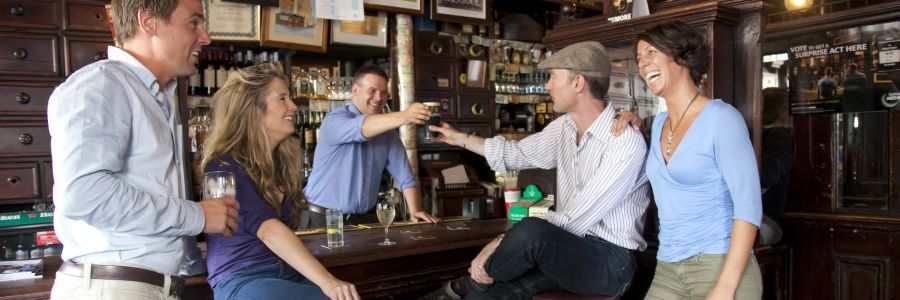 People toasting the Barman in a pub in Ireland. Enjoy a pub culture tour of Ireland with Discover Ireland Tours.